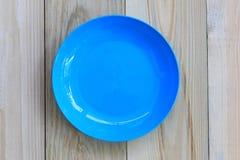Der blaue Teller, der auf Bretterboden leer ist und haben Kopienraum lizenzfreie stockfotos