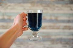 Der blaue thailändische Tee, der in einer Glasschale in ausgestreckter Hand auf Licht anchan ist, streifte hölzernen Hintergrund  Lizenzfreies Stockfoto