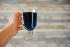 Der blaue thailändische Tee, der in einer Glasschale in ausgestreckter Hand auf Licht anchan ist, streifte hölzernen Hintergrund  Lizenzfreie Stockfotografie