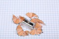 Der Bleistiftspitzer und Bleistift, die Rest auf Quadrate rasieren, bedecken Stockfotos