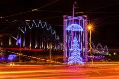 Der Blendungs-Weihnachtsbaum, der durch den Tanz des Lichtes umgeben wird, schleppt vom Verkehr im Stadtzentrum von Riga Stockfotos