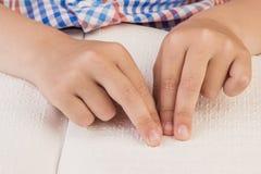 Der blinde Junge liest ein Buch, das auf Blindenschrift geschrieben wird Stockfotos
