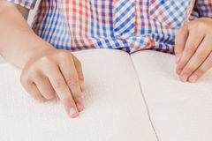 Der blinde Junge liest ein Buch, das auf Blindenschrift geschrieben wird Stockbilder