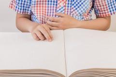 Der blinde Junge liest ein Buch, das auf Blindenschrift geschrieben wird Stockfoto