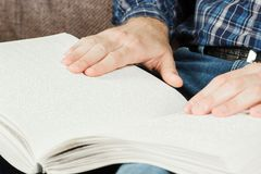 Der Blinder las ein Buch, das auf Blindenschrift geschrieben wurde Berühren Sie Ihr Stockfoto