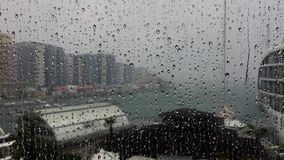 Der Blitz, der durch Regen gesehen wird, fällt auf das Fenster