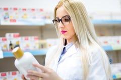 Der blonde Apotheker, der Pillen betrachtet und sahnt im Speicher Weibliche Assistenzarztlesung auf Aufklebern lizenzfreie stockbilder