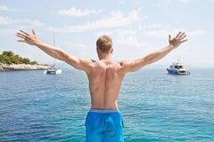 Der blonde hübsche junge Mann, der auf einem Segelboot steht - bereiten Sie zu J vor Lizenzfreies Stockfoto