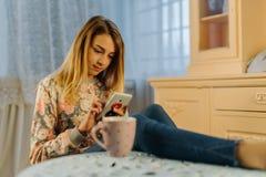 Der blonde Jugendliche surft das Netz über den Handy Lizenzfreie Stockbilder