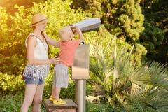 Der blonde Junge, der in einem großen Paar Ferngläsern schaut, bemuttern in der Nähe Park im Hintergrund Lizenzfreie Stockbilder