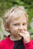 Der blonde Junge frühstückt draußen Stockbilder