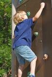 Der blonde Junge klettert den Kletterwand. Stockbild