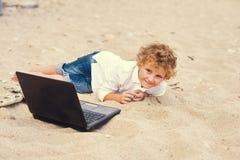 Der blonde Junge liegt auf dem Sand mit einem Laptop Stockfotos