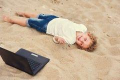 Der blonde Junge liegt auf dem Sand mit einem Laptop Lizenzfreie Stockbilder