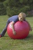 Der blonde Junge liegt auf einem entspannenden Ballon Stockfotografie