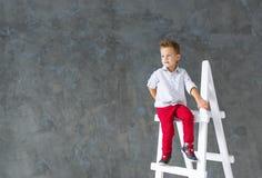 Der blonde Junge sitzt auf einem Bockleiter Lizenzfreies Stockbild