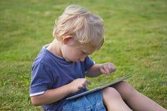 Der blonde Junge spielt mit der PC-Tablette draußen Stockfoto