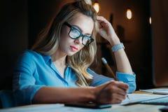 Der blonde kaukasische Student in den Brillen etwas mit Bleistift schreibend und studierend bebauen spät Stockbild