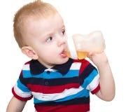 Der blonde kleine Junge, der Europäer, trinkt Saft von einer Inspektion Lizenzfreies Stockbild
