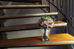 Der Blumenstrauß der Braut in einem Vase auf der Treppe Stockbilder