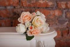Der Blumenstrauß von den Rosen, die auf dem Kamin liegen Lizenzfreie Stockfotos