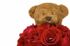 Der Blumenstrauß von roten Rosen, die silbernes Diamantringinnere mit unscharfem Teddybären haben stockfotografie