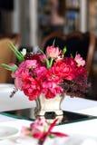 Der Blumenstrauß von roten und rosa Rosen, von Pfingstrosen mit Trauben und von Granatäpfeln in der niederländischen Art Lizenzfreie Stockfotografie