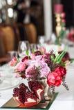 Der Blumenstrauß von roten und rosa Rosen, von Pfingstrosen mit Trauben und von Granatäpfeln in der niederländischen Art Stockfotografie