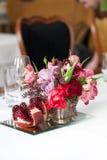 Der Blumenstrauß von roten und rosa Rosen, von Pfingstrosen mit Trauben und von Granatäpfeln in der niederländischen Art Lizenzfreie Stockfotos