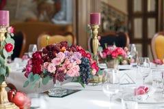 Der Blumenstrauß von roten und rosa Rosen, von Pfingstrosen mit Trauben und von Granatäpfeln in der niederländischen Art Stockfotos