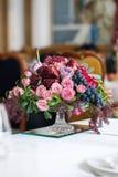 Der Blumenstrauß von roten und rosa Rosen, von Pfingstrosen mit Trauben und von Granatäpfeln in der niederländischen Art Stockbilder