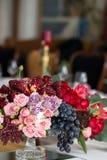 Der Blumenstrauß von roten und rosa Rosen, von Pfingstrosen mit Trauben und von Granatäpfeln in der niederländischen Art Stockbild