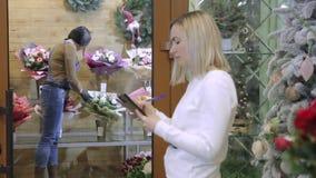 Der Blumenverkäufer zählt die Waren in der Lagerung der Anordnung nach stock video footage