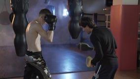 Der Boxer erfüllt die Schläge zusammen mit dem Trainer Ein Sportkerl in den Boxhandschuhen auf Verpackentatzen, Züge ein Schlag E stock video