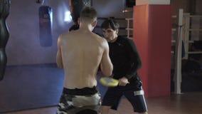 Der Boxer erfüllt die Schläge zusammen mit dem Trainer Ein Sportkerl in den Boxhandschuhen auf Verpackentatzen, Züge ein Schlag E stock video footage