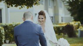 Der Bräutigam betrachtet die lächelnde Braut, die, ihr Hochzeitskleid zeigend stock video