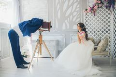 Der Bräutigam fotografiert die Braut auf einer Weinlesekamera stockfoto