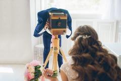 Der Bräutigam fotografiert die Braut auf einer Weinlesekamera stockfotografie