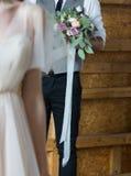 Der Bräutigam gibt den Braut ` s Blumenstrauß Lizenzfreie Stockfotografie