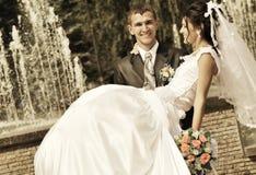 Der Bräutigam hält die Braut auf Händen an Stockfotografie