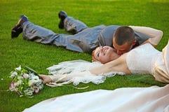 Der Bräutigam küßt die Braut, die auf einem Gras liegt Stockfoto