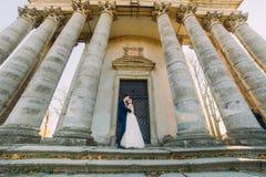 Der Bräutigam küsst die Braut auf dem Kopf bei der Stellung nahe dem Altbau Stockfotos