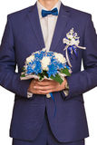 Der Bräutigam kostet mit einem Blumenstrauß auf Blumen für die Braut Lizenzfreie Stockfotografie