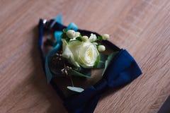 Der Bräutigam ` s Blumenstrauß liegt auf dem Boden nahe dem Schmetterling Stockfotografie