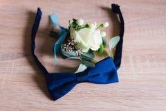 Der Bräutigam ` s Blumenstrauß liegt auf dem Boden nahe dem Schmetterling Lizenzfreie Stockfotografie