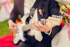 Der Bräutigam spielt Gitarre Lizenzfreie Stockfotos