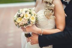 Der Bräutigam umfasst die Braut ` s Taille, einen Hochzeitsblumenstrauß in ihren Händen, Nahaufnahme, im Fokus ein Blumenstrauß,  Lizenzfreie Stockfotografie