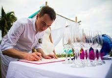 Der Bräutigam unterzeichnet Dokumente auf Ausrichtung der Heirat Ein Jungepaar unterzeichnet die Hochzeitsdokumente Der Mann unte lizenzfreie stockfotografie