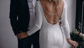 Der Br?utigam in einem Anzug umarmt die Braut in einem Heiratskleid lizenzfreie stockfotos