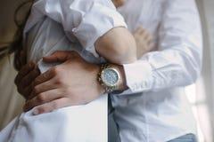 Der Br?utigam in einem Anzug umarmt die Braut in einem Heiratskleid lizenzfreies stockbild